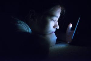 Teenager checking her phone at night