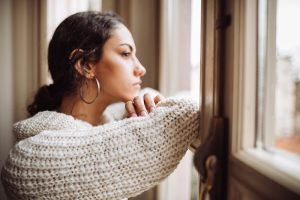 Sad young woman looking out the window
